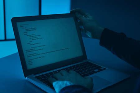 Hombre usando la computadora portátil en la mesa en una habitación oscura, primer plano. Ofensa criminal
