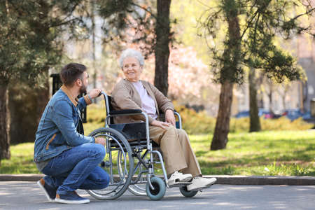 Senior woman in wheelchair with young man at park Imagens