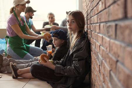 Teenager-Mädchen mit anderen armen Menschen, die Essen von Freiwilligen im Haus erhalten receiving Standard-Bild