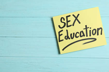 Note with phrase SEX EDUCATION on light blue wooden background, top view. Space for text