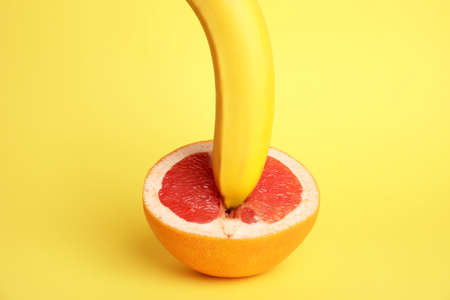 Fresh grapefruit and banana on yellow background. Sex concept