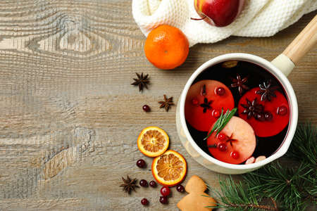 Saucepan with tasty mulled wine on wooden background, flat lay. Space for text
