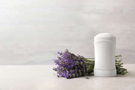 Female deodorant and lavender flowers on marble table. Space for text