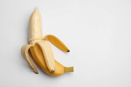 Banana with condom on white background, top view. Safe sex