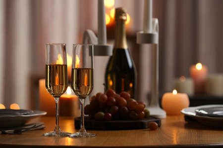 Glasses of champagne on wooden table against blurred burning candles