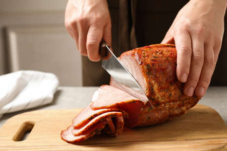 Woman cutting ham on wooden board at table, closeup