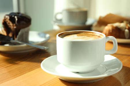 Tasse frischen aromatischen Kaffee und Cupcake am Tisch im Café