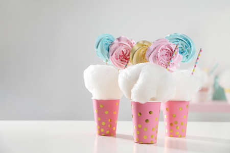 Cups with cotton candy dessert on table, space for text Imagens