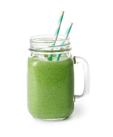 Tarro de masón de batido verde saludable con espinacas frescas sobre fondo blanco.