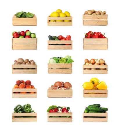 Conjunto de cajas de madera con diferentes frutas, verduras y huevos sobre fondo blanco. Foto de archivo