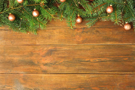 Fir tree branches with Christmas decoration on wooden background, flat lay. Space for text Reklamní fotografie