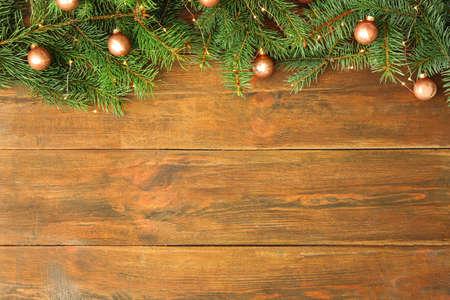 Rami di abete con decorazioni natalizie su fondo in legno, distesi piatti. Spazio per il testo Archivio Fotografico