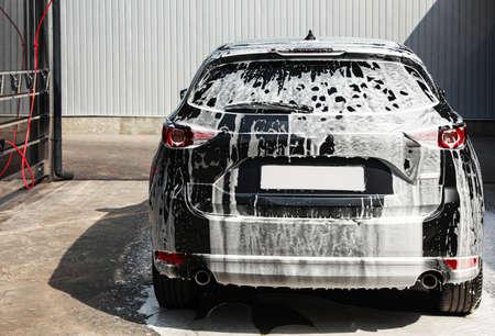 Luxe auto bedekt met schuim bij wasstraat, achteraanzicht