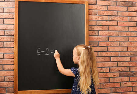 Cute little left-handed girl doing sums on chalkboard near brick wall