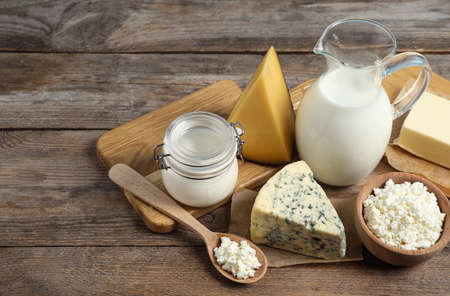 Different delicious dairy products on wooden table