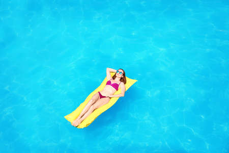 Young woman on inflatable mattress in swimming pool, above view Stock Photo