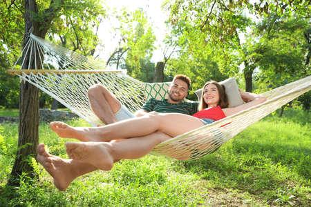 Pareja joven descansando en una cómoda hamaca en el jardín verde Foto de archivo