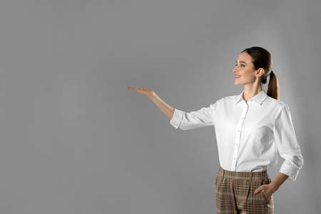 Portrait of young female teacher on grey background. Space for text Stok Fotoğraf