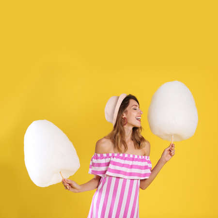 Happy young woman with cotton candies on yellow background