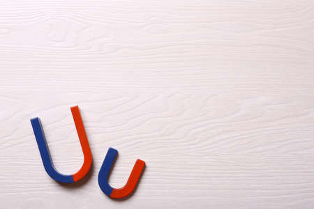 Red and blue horseshoe magnets on light wooden background, flat lay. Space for text Stock Photo