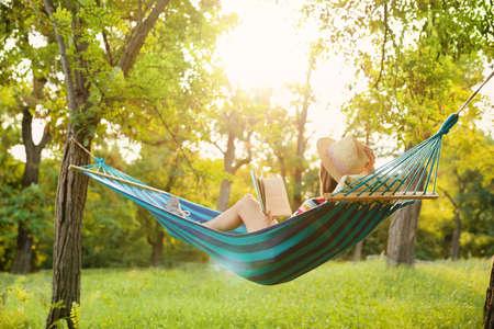 Jonge vrouw leesboek in comfortabele hangmat in groene tuin
