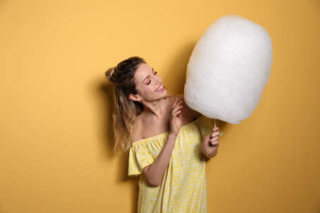 Portrait of young woman with cotton candy on yellow background