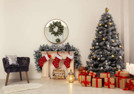 Stylish Christmas interior with decorated fir tree and fireplace