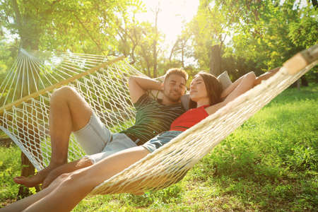Young couple resting in comfortable hammock at green garden