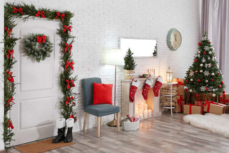 Stylish interior with beautiful Christmas tree and decorative fireplace