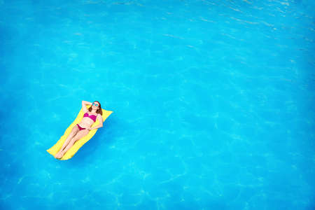 Young woman on inflatable mattress in swimming pool, above view Stock fotó