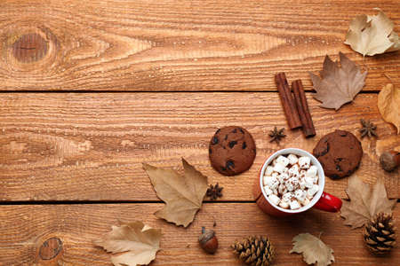 Flat lay composition with cup of hot drink on wooden table, space for text. Cozy autumn atmosphere