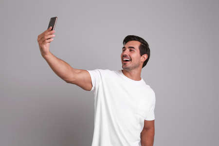 Handsome young man taking selfie with smartphone on grey background Banque d'images - 132555566