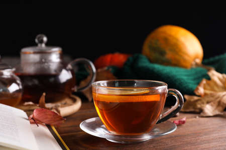 Cup of hot drink on wooden table against black background. Cozy autumn atmosphere