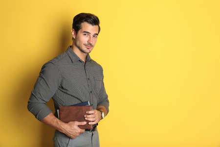 Young male teacher with books on yellow background. Space for text