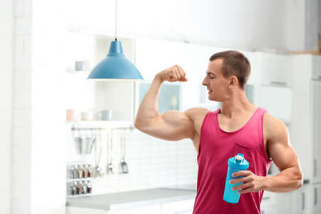 Athletic young man with protein shake in kitchen