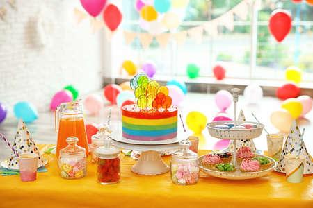 Pastel de cumpleaños brillante y otras delicias en la mesa en la habitación decorada Foto de archivo