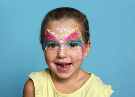 Cute little girl with face painting on blue background