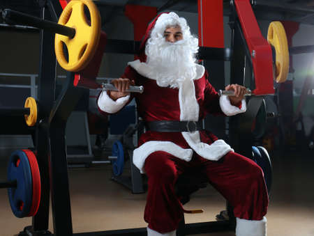 Young Santa Claus training in modern gym Stock Photo