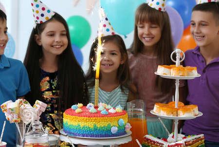 Glückliche Kinder in der Nähe von Kuchen mit Feuerwerkskerze auf der Geburtstagsfeier im Haus Standard-Bild