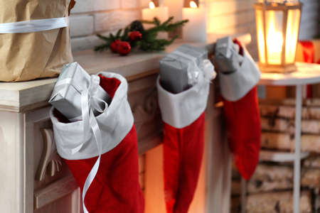 Red Christmas stockings with gifts on decorative fireplace indoors. Festive interior Archivio Fotografico