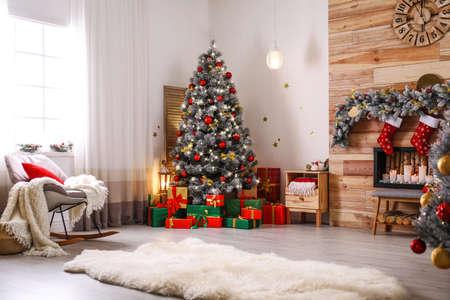 Interior de habitación elegante con hermoso árbol de Navidad y chimenea decorativa
