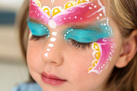 Cute little girl with face painting indoors, closeup Stockfoto