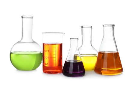 Cristalería de laboratorio con líquidos de color sobre fondo blanco.