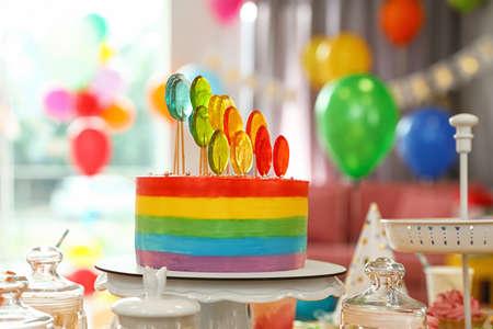 Torta di compleanno brillante e altre prelibatezze sul tavolo nella stanza decorata
