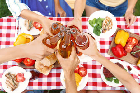 Friends with drinks at barbecue party outdoors, above view