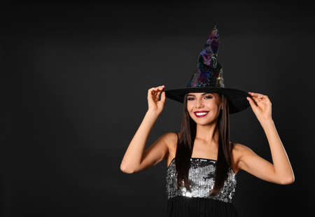 Beautiful woman wearing witch costume for Halloween party on black background, space for text Stockfoto