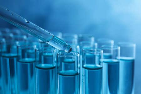 Upuszczenie próbki do probówki z płynem na niebieskim tle, zbliżenie