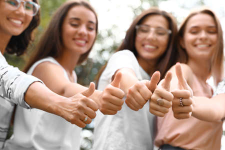 Happy women showing thumbs up outdoors, focus of hands. Girl power concept
