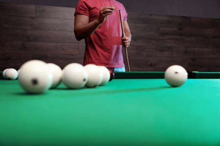 Young man chalking cue near billiard table indoors, closeup