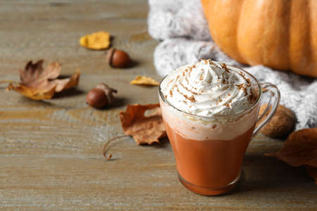 Pumpkin spice latte with whipped cream in glass cup on wooden table. Space for text Banco de Imagens